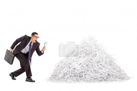 Businessman examining pile of shredded paper