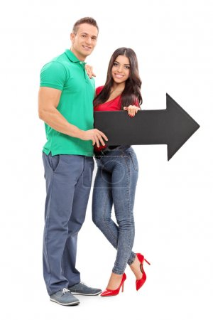 Young couple holding an arrow pointing right