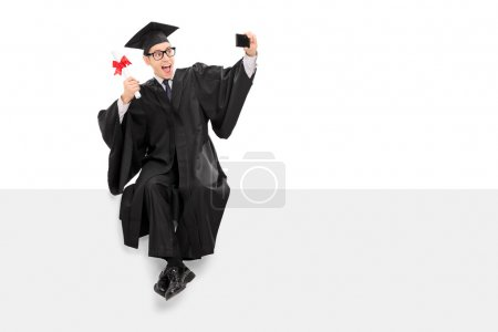 College graduate taking selfie