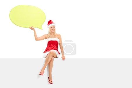 Female in Santa costume holding speech bubble