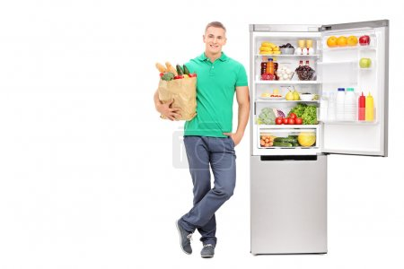 Man standing by open refrigerator