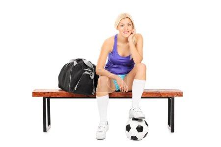 Foto de Female soccer player sitting on a bench isolated on white background - Imagen libre de derechos