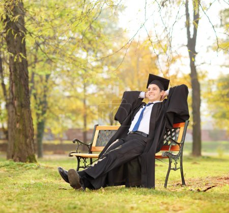 Graduate student on bench in park