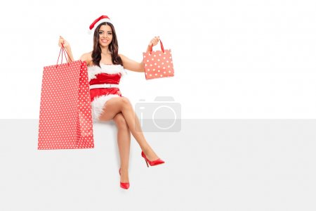 Woman in Santa costume holding shopping bags