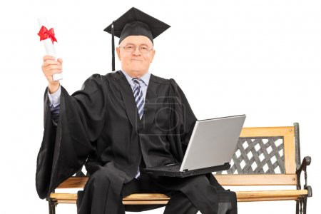 Photo for Proud mature graduate holding a diploma seated on a bench isolated on white background - Royalty Free Image