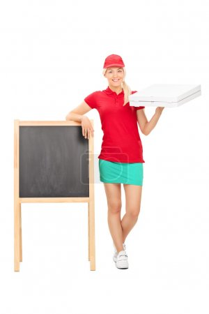 Photo for Full length portrait of a pizza delivery girl standing by a blank blackboard isolated on white background - Royalty Free Image