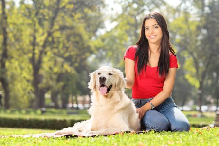 Girl sitting in park with dog