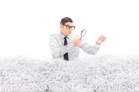 Man examining pile of shredded paper