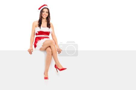 Female Santa sitting on signboard