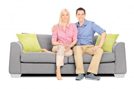 Photo for Young couple sitting on a modern sofa isolated on white background - Royalty Free Image