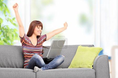 Photo pour Heureuse femme travaillant sur ordinateur portable et gesticulant bonheur assise sur un canapé à la maison - image libre de droit