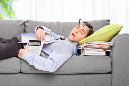 Tired employee sleeping on sofa