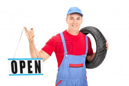 Male mechanic holding open sign
