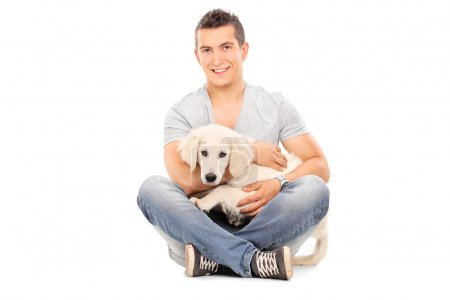 Photo for Man with his baby dog seated on floor isolated on white background - Royalty Free Image