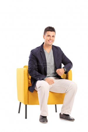 Photo for Smiling man sitting on a modern chair isolated on white background - Royalty Free Image