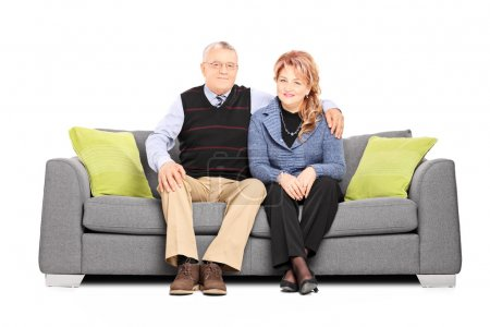 Mature couple seated on sofa