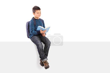 Photo pour Écolier lisant un livre assis sur un panneau vierge isolé sur fond blanc - image libre de droit