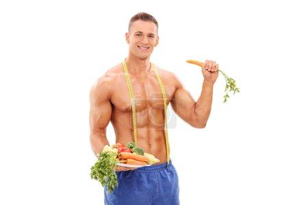 Foto de Atleta joven sosteniendo un plato con verduras aisladas sobre fondo blanco - Imagen libre de derechos