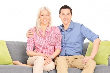 Photo for Young couple sitting on a modern sofa isolated against white background - Royalty Free Image