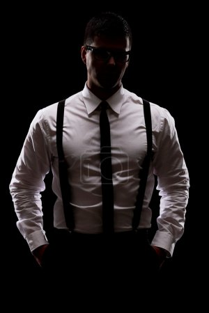 Photo for Vertical shot of a mysterious man standing in the dark on black background - Royalty Free Image