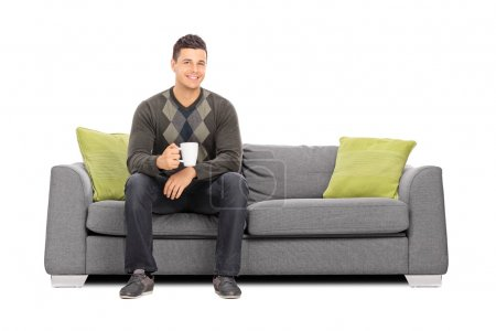 Photo for Young man holding a cup of coffee seated on sofa isolated on white background - Royalty Free Image