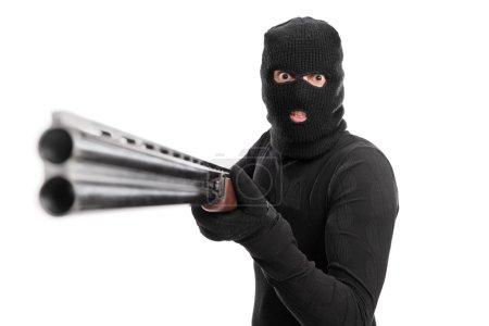 Angry criminal pointing a shotgun