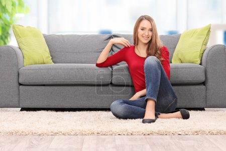 Photo for Relaxed young woman sitting by a sofa at home - Royalty Free Image