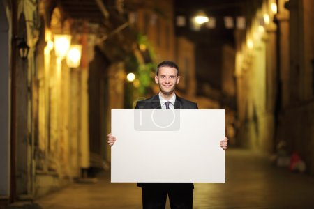 Businessman holding panel in city street
