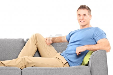 Photo for Relaxed young man sitting on a sofa isolated on white background - Royalty Free Image