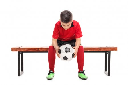 Worried boy in football shirt