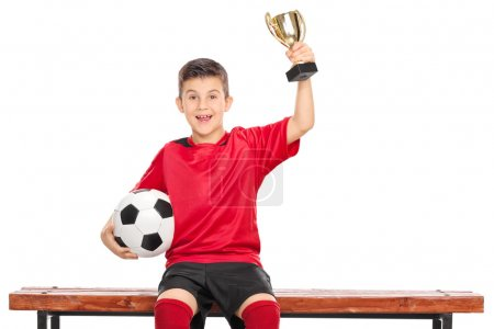 Photo for Delighted boy in soccer dress holding a trophy in one hand and a ball in the other, seated on a wooden bench isolated on white background - Royalty Free Image