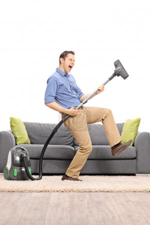 Guy playing guitar on a vacuum cleaner