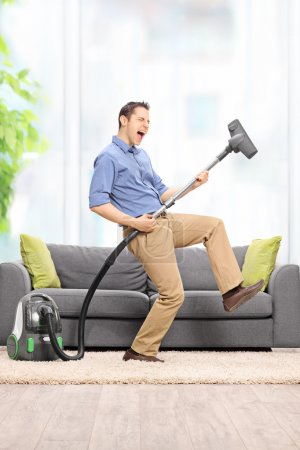 Guy playing guitar on the vacuum cleaner