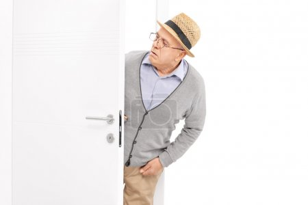 Senior looking at something behind a door
