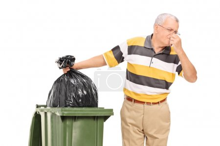 Senior throwing away bag of trash