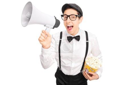Photo pour Jeune homme en tenue artistique tenant une boîte de pop-corn et parlant sur un mégaphone isolé sur fond blanc - image libre de droit