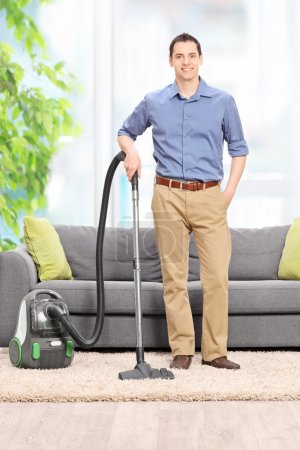 Photo for Full length portrait of a young man posing with a vacuum cleaner in front of a gray couch at home - Royalty Free Image