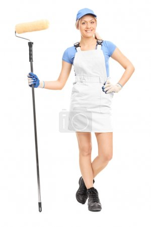 Photo for Full length portrait of a female house painter in a yellow uniform posing with a paint roller isolated on white background - Royalty Free Image
