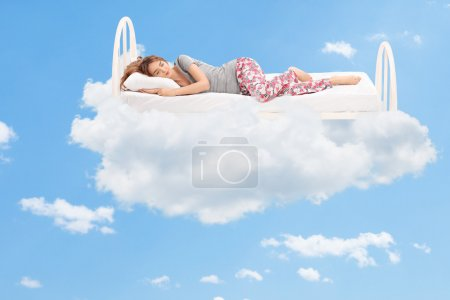 Photo for Relaxed young woman sleeping on a comfortable bed in the clouds - Royalty Free Image