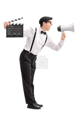 Photo pour Profil complet d'un jeune réalisateur tenant un clapet et criant sur un mégaphone isolé sur fond blanc - image libre de droit