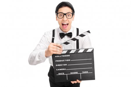 Photo for Excited movie director with glasses holding a movie clapperboard and looking at the camera isolated on white background - Royalty Free Image