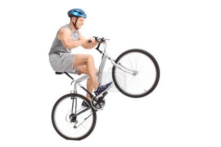 Joyful young biker doing a wheelie