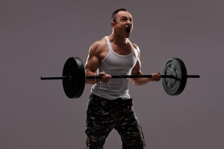 Determined young athlete exercising with a barbell