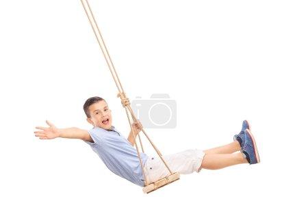 Joyful little boy swinging on a swing
