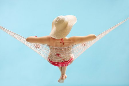 Young girl with a stylish hat lying in a hammock