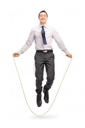 Young cheerful businessman jumping a rope