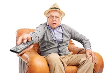 Photo pour Homme âgé en colère appuyant sur des boutons sur une télécommande assise dans un fauteuil isolé sur fond blanc - image libre de droit