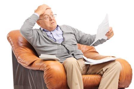 Photo pour Gentilhomme de haut choqué en regardant ses factures dans l'incrédulité, assis dans un fauteuil isolé sur fond blanc - image libre de droit