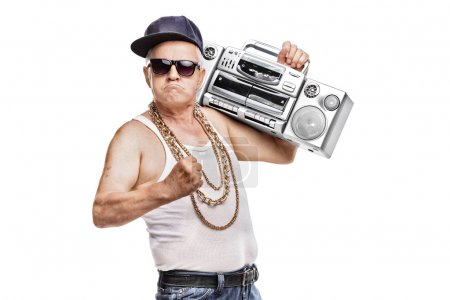 Photo for Mature man in hip-hop outfit holding a ghetto blaster and looking at the camera isolated on white background - Royalty Free Image