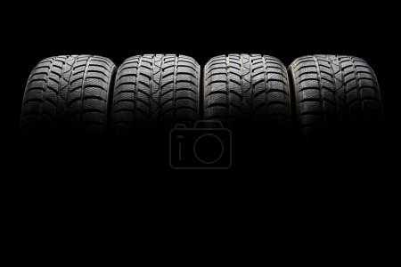 Photo for Studio shot of a set of four black car tires lined up horizontally in a dark ambient on black background - Royalty Free Image
